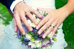 Mains et anneaux sur le bouquet de mariage Image libre de droits