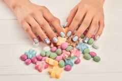 Mains et bonbons manicured par femme Images libres de droits