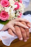 Mains et boucles avec le bouquet de mariage Image stock