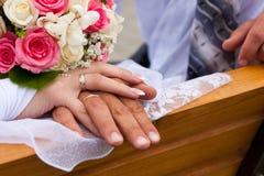 Mains et boucles avec le bouquet de mariage Images stock