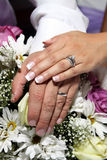 Mains et boucles de mariage sur des fleurs Photographie stock libre de droits