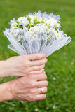 Mains et boucles sur le bouquet de mariage Photographie stock