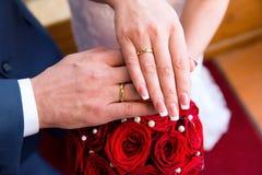 Mains et boucles sur le bouquet de mariage Image stock