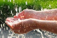 Mains et eau photo stock