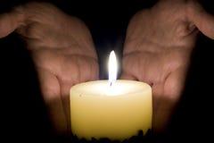 Mains et lumière humaines de bougie Photographie stock libre de droits