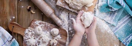 Mains et pâte du ` s d'enfants avec de la farine sur une table en bois et une serviette, une goupille et un conseil verts photos stock