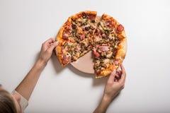 Mains et pizza femelles de plat Photos stock