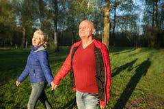Mains et promenade heureuses de prise de couples d'aînés ; Photo stock