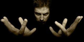 Mains et visage de magicien mauvais dans l'obscurité Photos stock