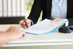 Mains exécutives indiquant où signer le contrat Photo stock