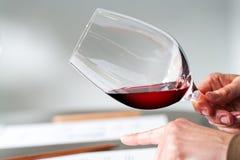 Mains examinant la densité de vin à l'échantillon Images stock