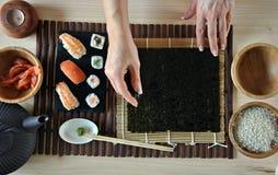 Mains faisant cuire des sushi Photo libre de droits