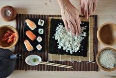 Mains faisant cuire des sushi Image libre de droits