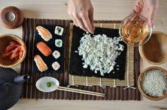 Mains faisant cuire des sushi Photos libres de droits