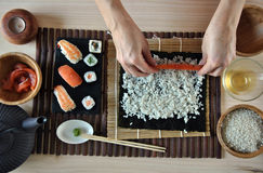 Mains faisant cuire des sushi Photo stock
