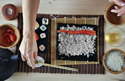 Mains faisant cuire des sushi Image stock