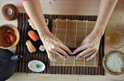 Mains faisant cuire des sushi Images stock