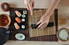 Mains faisant cuire des sushi Photographie stock libre de droits