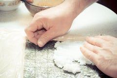 Mains faisant cuire des sushi avec du riz, des saumons et le nori Photos libres de droits