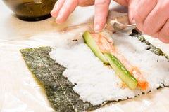 Mains faisant cuire des sushi avec du riz, des saumons et le nori Images stock