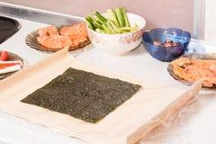 Mains faisant cuire des sushi avec du riz, des saumons et le nori Photo libre de droits