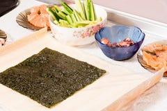 Mains faisant cuire des sushi avec du riz, des saumons et le nori Images libres de droits