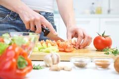 Mains faisant cuire la salade de légumes Image stock