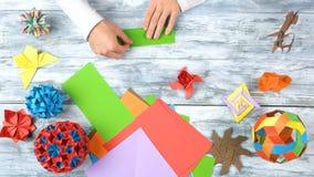 Mains faisant l'origami avec le Livre vert photos stock