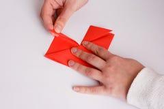 Mains faisant la fin de coeur d'origami sur le blanc Photo stock