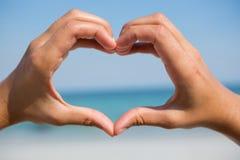 Mains faisant la forme de coeur à la plage Image stock