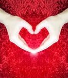 Mains faisant le coeur sur le fond pelucheux rouge Concept de jour du ` s de Valentine Concept d'amour Paix Photos stock