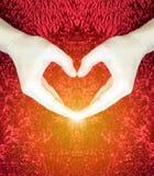 Mains faisant le coeur sur le fond pelucheux rouge Concept de jour du ` s de Valentine Concept d'amour Paix Photographie stock