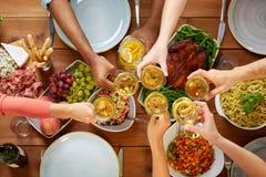 Mains faisant tinter des verres de vin au-dessus de table avec la nourriture Photographie stock