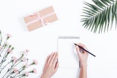 Mains femelles écrivant dans un carnet, composition de fête Photo stock