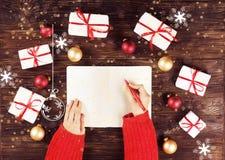 Mains femelles écrivant la liste de cadeau de Noël dans le carnet sur le fond en bois avec des cadeaux et des labels Photo modifi Image libre de droits