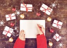 Mains femelles écrivant la liste de cadeau de Noël dans le carnet sur le fond en bois avec des cadeaux et des labels Photo modifi Photographie stock