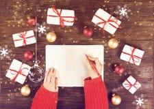 Mains femelles écrivant la liste de cadeau de Noël dans le carnet sur le fond en bois avec des cadeaux et des labels Photo modifi Image stock