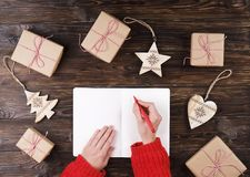 Mains femelles écrivant la liste de cadeau de Noël sur le papier sur le fond en bois avec des cadeaux et des labels Photo libre de droits