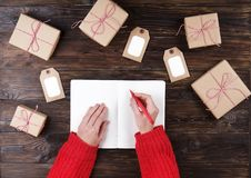 Mains femelles écrivant la liste de cadeau de Noël sur le papier sur le fond en bois avec des cadeaux et des labels Image libre de droits