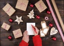 Mains femelles écrivant la liste de cadeau de Noël sur le papier sur le fond en bois avec des cadeaux et des labels Photographie stock libre de droits