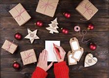Mains femelles écrivant la liste de cadeau de Noël sur le papier sur le fond en bois avec des cadeaux et des labels Images libres de droits