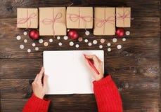 Mains femelles écrivant la liste de cadeau de Noël sur le papier sur le fond en bois avec des cadeaux et des labels Photo stock