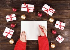 Mains femelles écrivant la liste de cadeau de Noël sur le papier sur le fond en bois avec des cadeaux et des labels Image stock