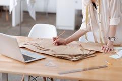 Mains femelles écrivant sur un robe-modèle Images libres de droits