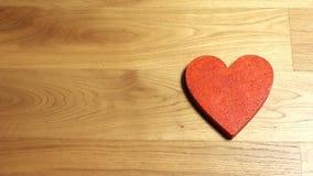Mains femelles élégantes mettant deux formes rouges de coeur sur la table en bois Aimez, jour du ` s de Valentine, unité, famille banque de vidéos
