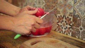 Mains femelles épluchant les tomates bouillies dans la cuisine banque de vidéos