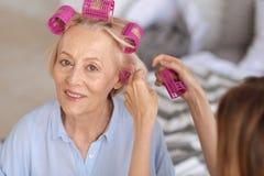 Mains femelles aidant à mettre dessus des rouleaux de cheveux Photo stock
