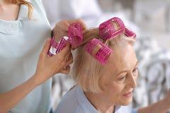 Mains femelles attachant les rouleaux roses de cheveux Photographie stock