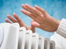 Mains femelles au-dessus de l'appareil de chauffage Photo stock