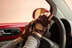 Mains femelles avec des machines de volant de conducteur de gants photos libres de droits